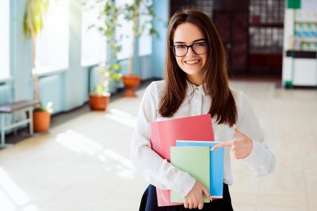 Retrato de niña morena inteligente, inteligente y encantadora en blusa blanca casual y gafas, sosteniendo libros