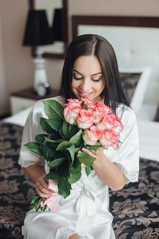 Retrato de niña morena que se sienta en una cama con un ramo de rosas en la mañana