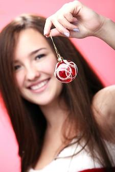 Retrato de una niña mostrando una bola de navidad