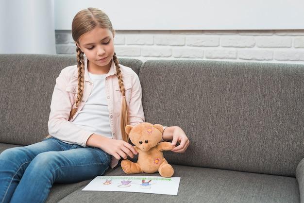 Retrato de una niña mostrando papel de dibujo familiar a su osito de peluche