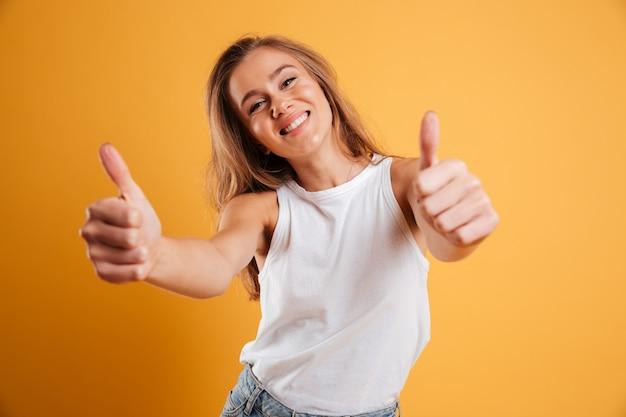 Retrato de una niña muy alegre mostrando los pulgares para arriba