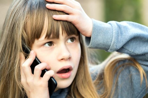 Retrato de niña niño estresado con el pelo largo hablando por teléfono celular. niña niño comunicarse mediante teléfono inteligente. concepto de comunicación infantil.