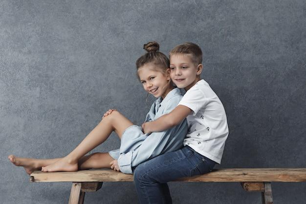 Un retrato de una niña y un niño en el gris