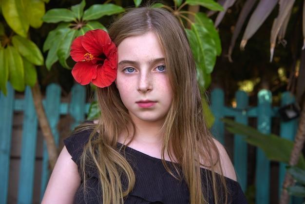 Retrato de niña niño rubio con flor roja
