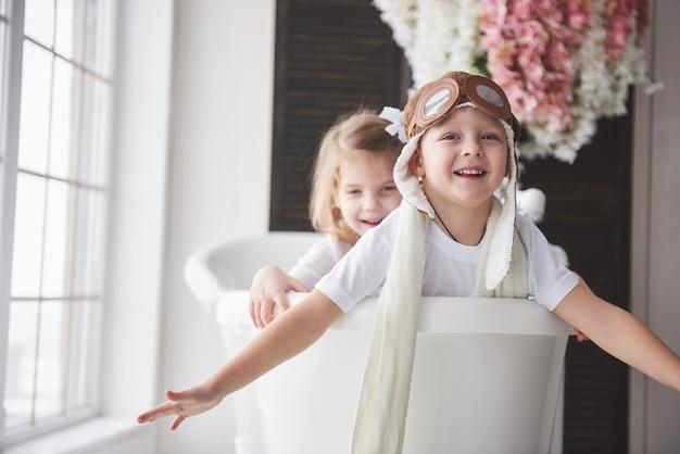 Retrato de una niña y un niño con sombrero de piloto jugando en el baño a los pilotos o marineros. viajes, infancia y realización de sueños.