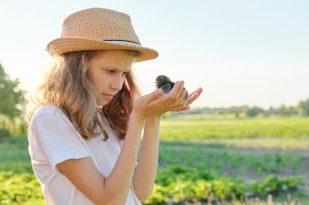 Retrato de niña niño sosteniendo pollitos recién nacidos en las manos