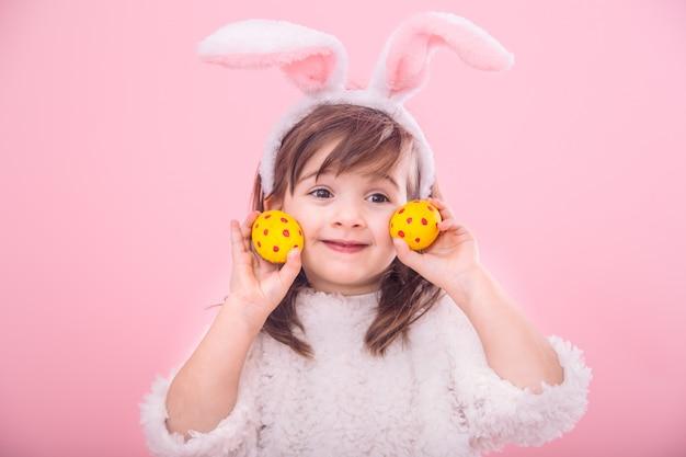 Retrato de una niña con orejas de conejo con huevos de pascua