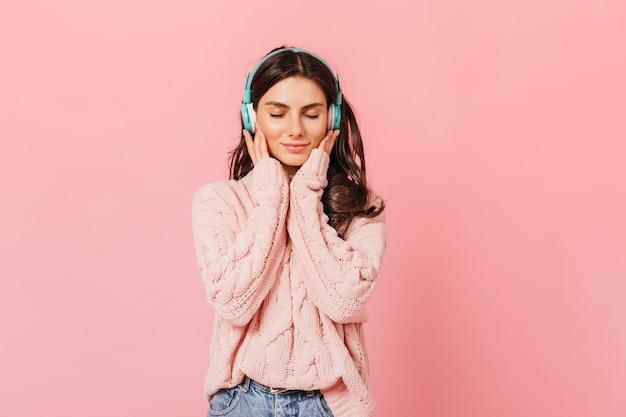 Retrato de niña pacificada escuchando agradable melodía en auriculares. señora en suéter lindo sonriendo con los ojos cerrados sobre fondo rosa.