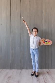 Retrato de una niña con paleta pintada y pincel de pie contra un tablón de madera gris