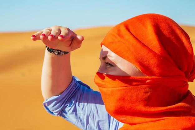 Retrato de una niña con un pañuelo en la cabeza. desierto del sahara, erg chebbi, merzouga, marruecos.