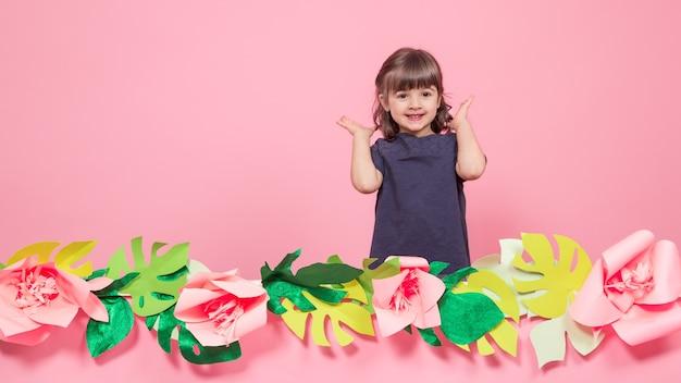 Retrato de una niña en una pared rosa de verano