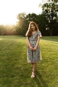 Retrato de una niña con pecas y cabello rojo. puesta de sol. chica alegre al atardecer del día. vestido de verano y buen humor. retrato de una niña. apariencia única
