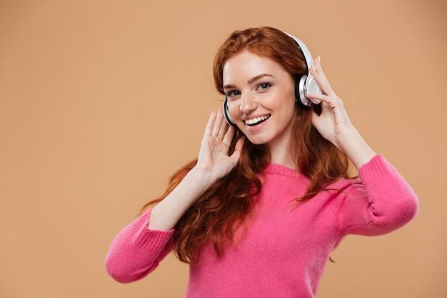 Retrato de una niña pelirroja amigable feliz escuchando música con auriculares