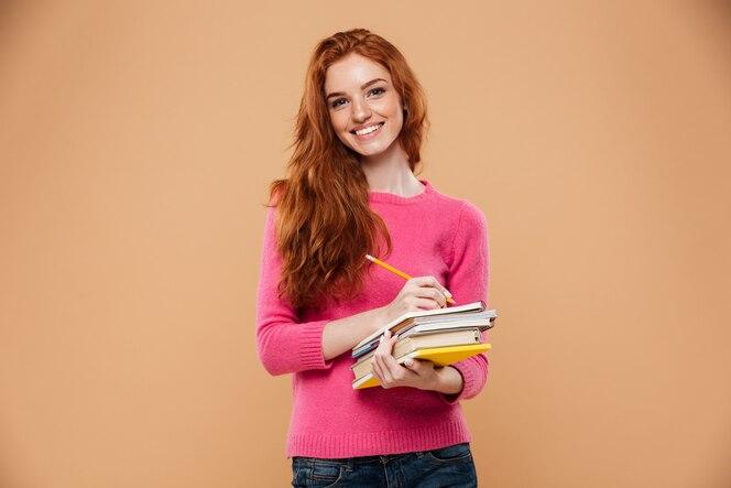 Retrato de una niña pelirroja bonita feliz sosteniendo libros