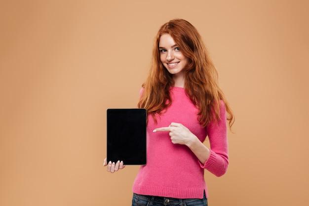 Retrato de una niña pelirroja joven sonriente que señala el dedo en tableta digital