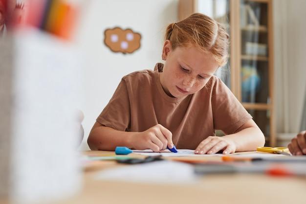 Retrato de niña pelirroja pecosa haciendo dibujos con lápices de colores mientras disfruta de la clase de arte en la escuela o centro de desarrollo