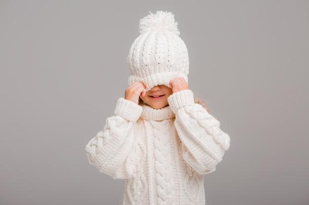 Retrato de una niña de pelo rizado en un gorro de invierno blanco de punto