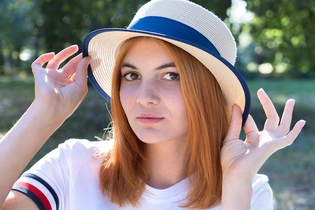 Retrato de una niña con el pelo rojo y sombrero amarillo al aire libre en el parque de verano.
