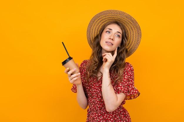 Retrato de una niña pensativa con un sombrero sobre un fondo amarillo