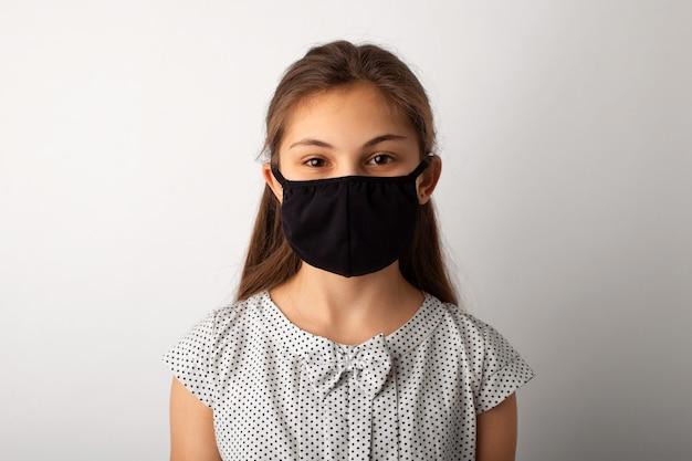 Retrato de una niña pequeña en máscara médica negra en estudio