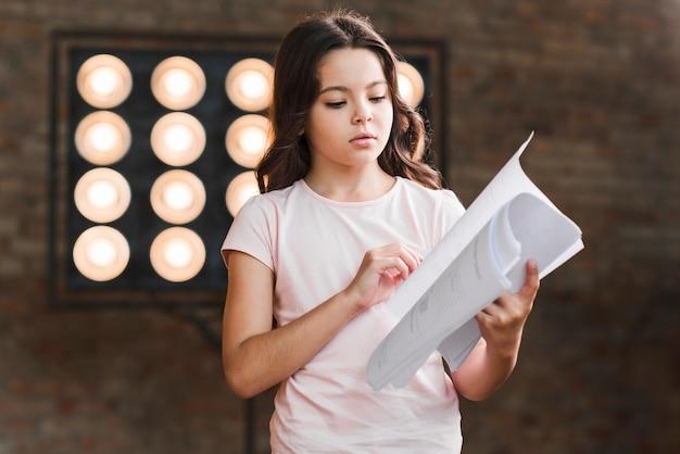 Retrato de niña de pie contra el escenario leyendo el guión