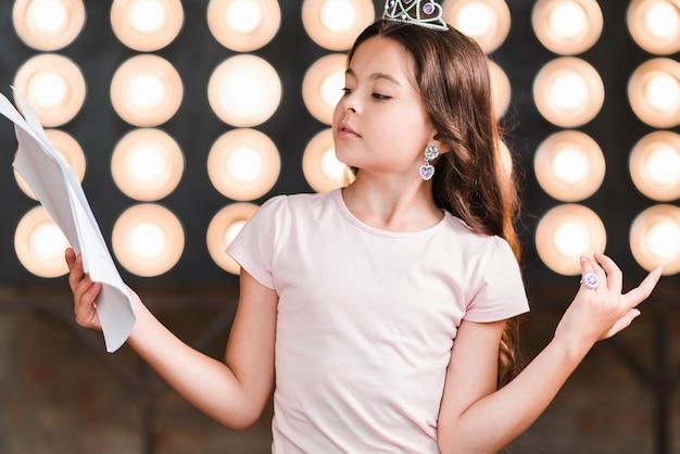 Retrato de niña de pie contra la luz del escenario mirando guiones encogiéndose de hombros