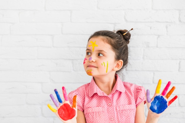 Retrato de una niña de pie contra la pared blanca que muestra las manos pintadas de colores mirando a otro lado