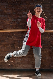 Retrato de una niña de pie contra la pared de ladrillo bailando