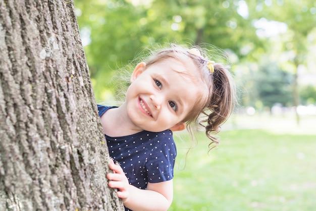 Retrato de una niña de pie detrás del árbol mirando a escondidas en el jardín