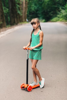 Retrato de una niña de pie en empuje scooter en la calle