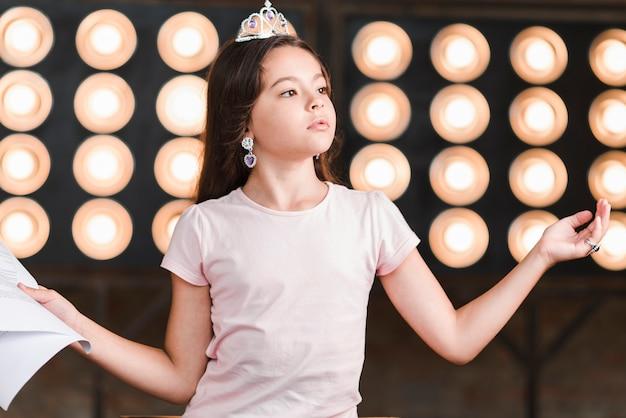 Retrato de una niña de pie ensayando frente a la luz de la etapa