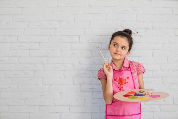 Retrato de una niña con pincel y paleta de pie contra la pared blanca