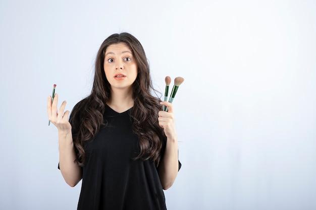 Retrato de niña con pinceles cosméticos mirando a cámara en blanco.