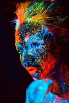 Retrato de una niña pintada en polvo fluorescente.