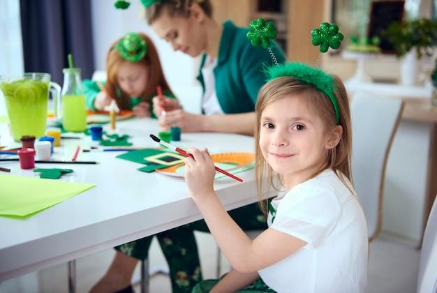 Retrato de niña pintando decoración en el día de san patricio