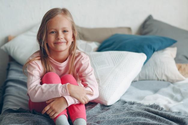 Retrato de niña positiva sentado en la cama y sonriendo