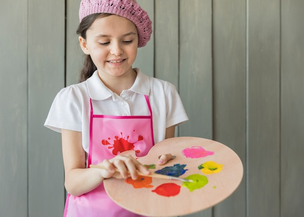 Retrato de una niña que mezcla el color en la paleta con pincel