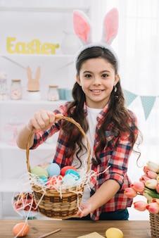 Retrato de una niña que muestra la canasta llena de coloridos huevos de pascua