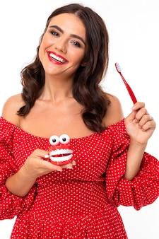 Retrato de una niña que muestra cómo cepillarse los dientes