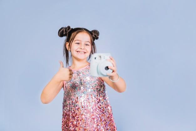Retrato de una niña que sostiene la cámara instantánea que muestra el pulgar hacia arriba de la muestra contra el fondo azul