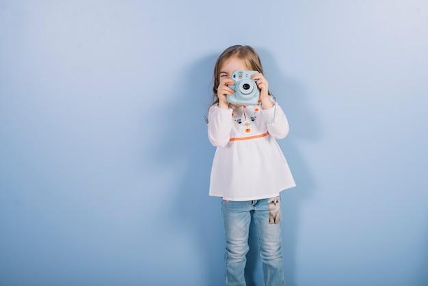 Retrato de una niña que toma una fotografía con una cámara instantánea vintage de pie contra el fondo azul