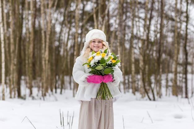 Retrato de una niña con un ramo de flores en el bosque en invierno