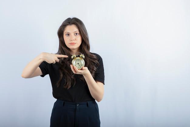 Retrato de niña con reloj despertador en gris.