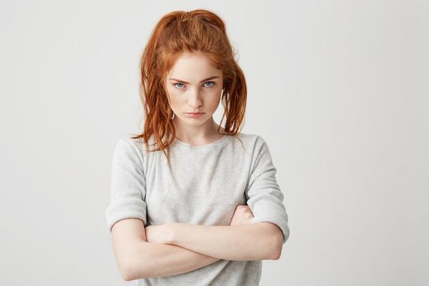 Retrato de niña resentida joven y bonita pelirroja brutalmente con los brazos cruzados.