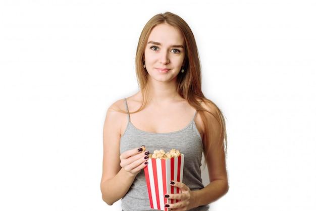 Retrato de una niña riendo en ropa casual con caja de palomitas de maíz