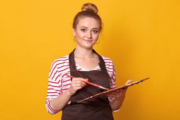Retrato de niña rubia artista sonriente con paleta de color en estudio de arte, atractiva joven vistiendo camisa casual a rayas y delantal marrón