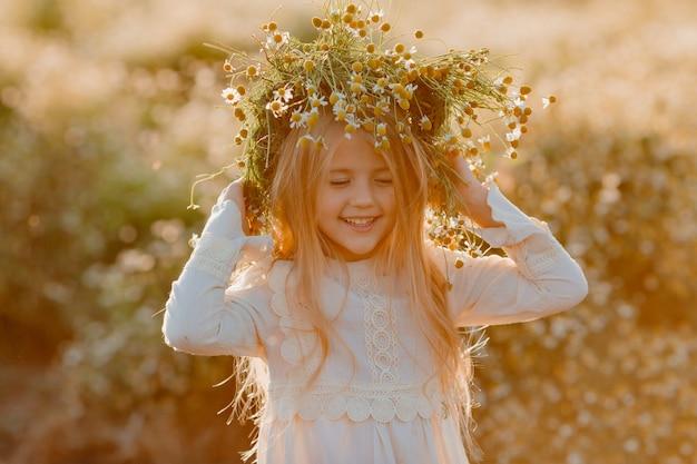 Retrato de una niña rubia con una corona de margaritas en la cabeza en el verano al atardecer