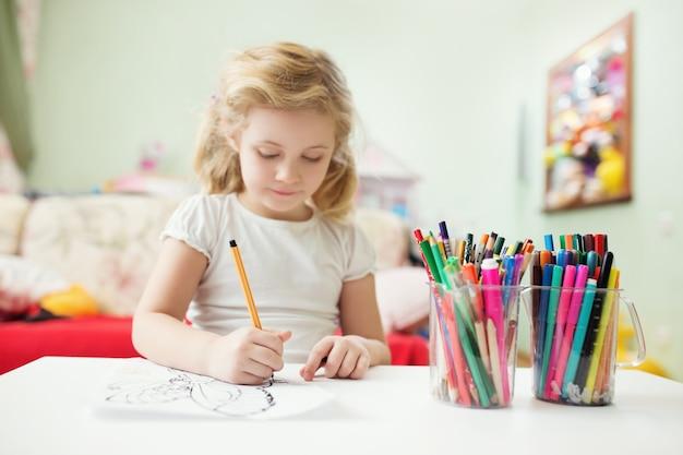 Retrato de niña rubia dibujo en casa en su habitación.