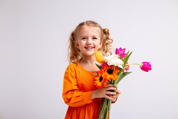 Retrato de una niña rubia con un ramo de flores de primavera en una pared de luz