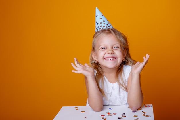 Retrato de una niña rubia en un sombrero festivo se regocija de fondo de color confeti